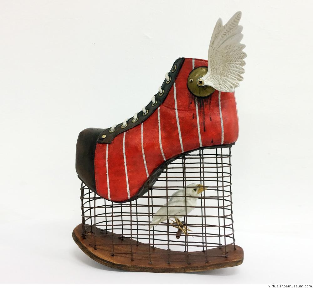 Rzeźba przypominająca but na koturnie, w koturnie zamontowana została klatka ze sztucznym ptakiem