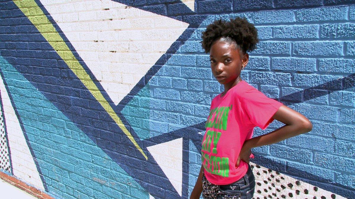 Dziewczynka w różowej bluzce na tle sciany z niebieskim graffiti