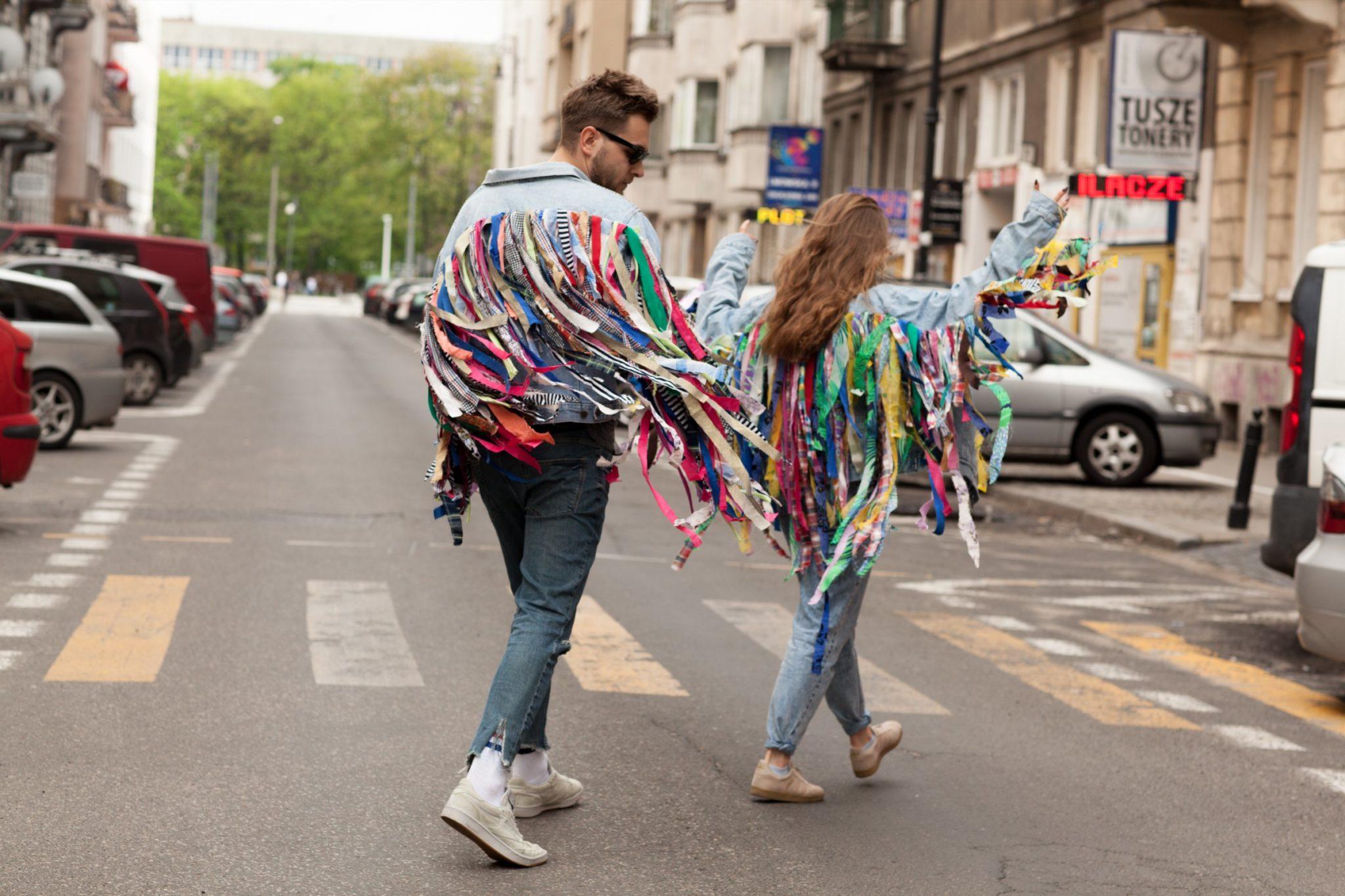 Mężczyzna i kobieta idący ulicą w kurtkach z doczepianymi, kolorowymi frędzlami