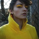 Dziewczyna w brązowych, krótkich włosach, ubrana w żółty płaszcz z podniesionym kołnieżem, z żółtymi kreskami na powiekach na tle ogrodzenia z siatki