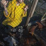 Dziewczyna ubrana w żółty płaszcz kuca przy siatce od ogrodzenia, po drugiej stronie są kury