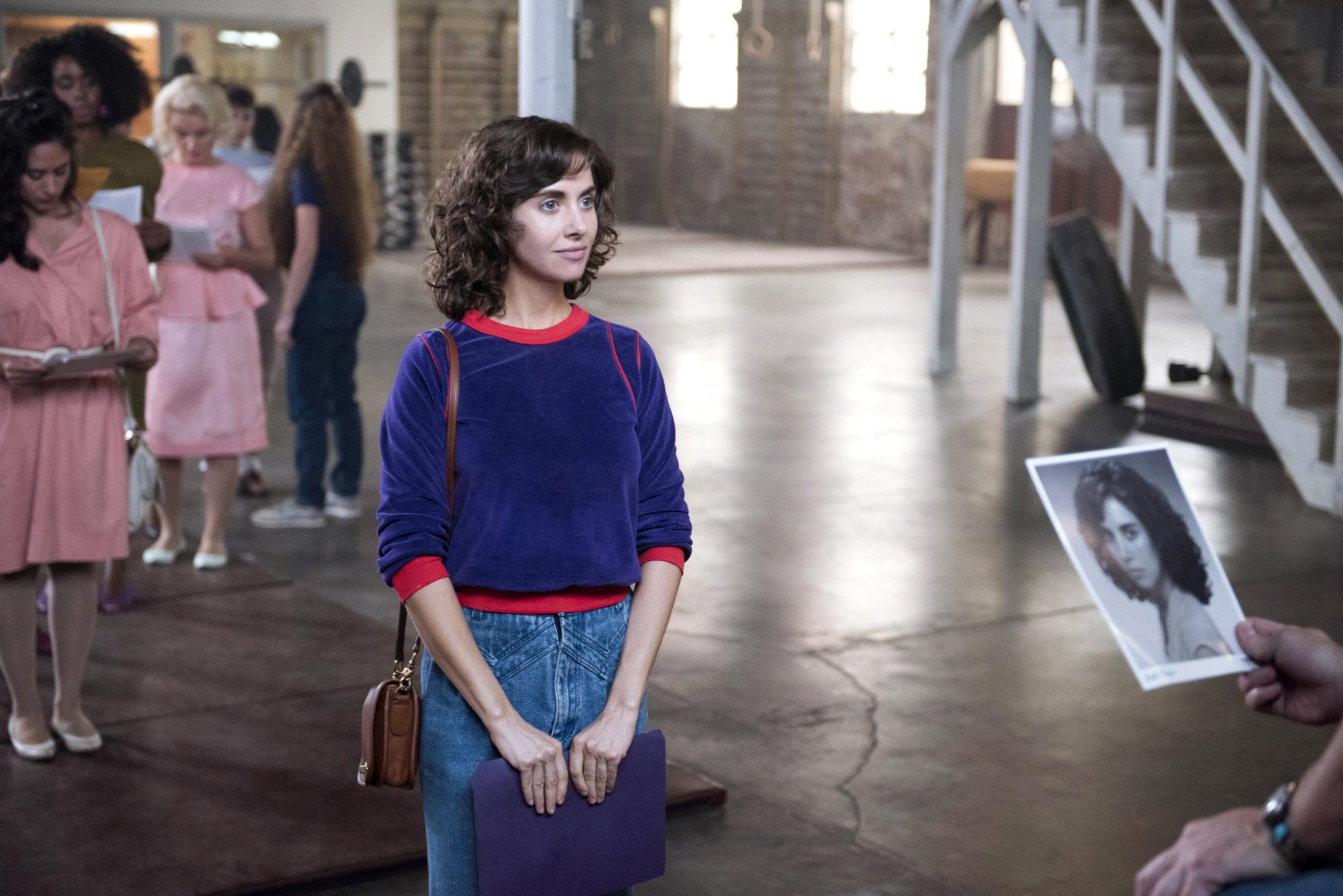 brunetka w niebieskiej bluzie z czerwonymi zakonczeniami i niebieskich jeansach o krotkich wlosach skonczyla stac w kolejce na opuszczonej sali starego magazynu w rekach trzyma portfolio