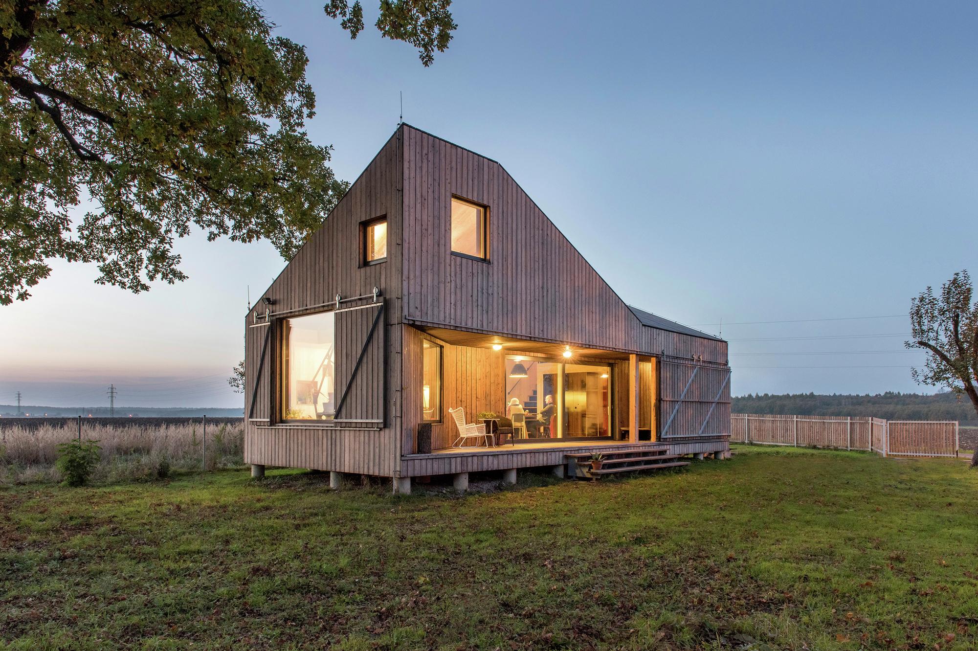 Fotografia kolorowa przedstawiająca mały drewniany dom na polanie