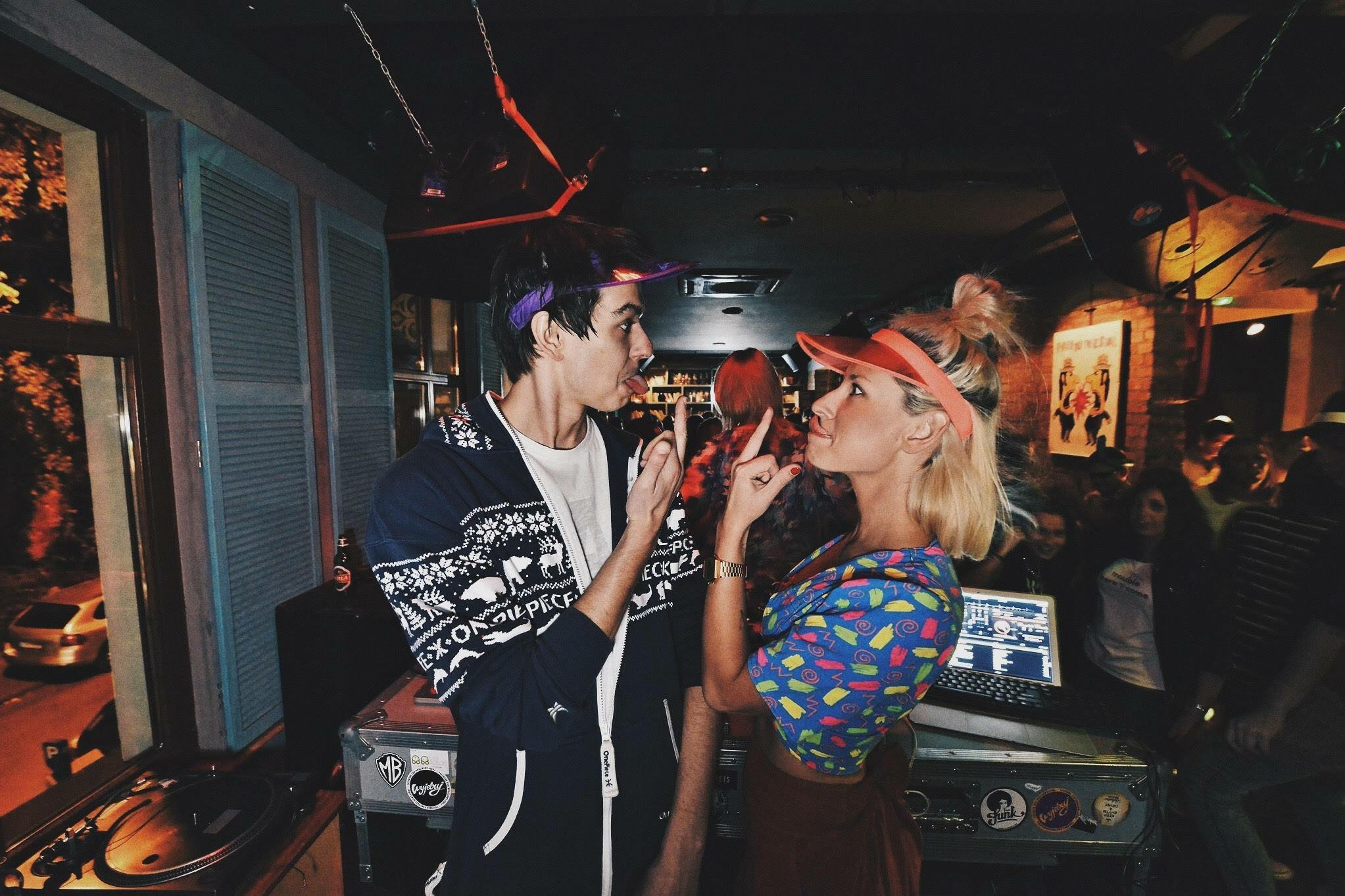 Na zdjęciu widzimy chłopaka i dziewczynę, którzy są w klubie i stoją za kontrolerem didżeja. Stoją do siebie przodem i nawzajem robią do siebie głupie miny.