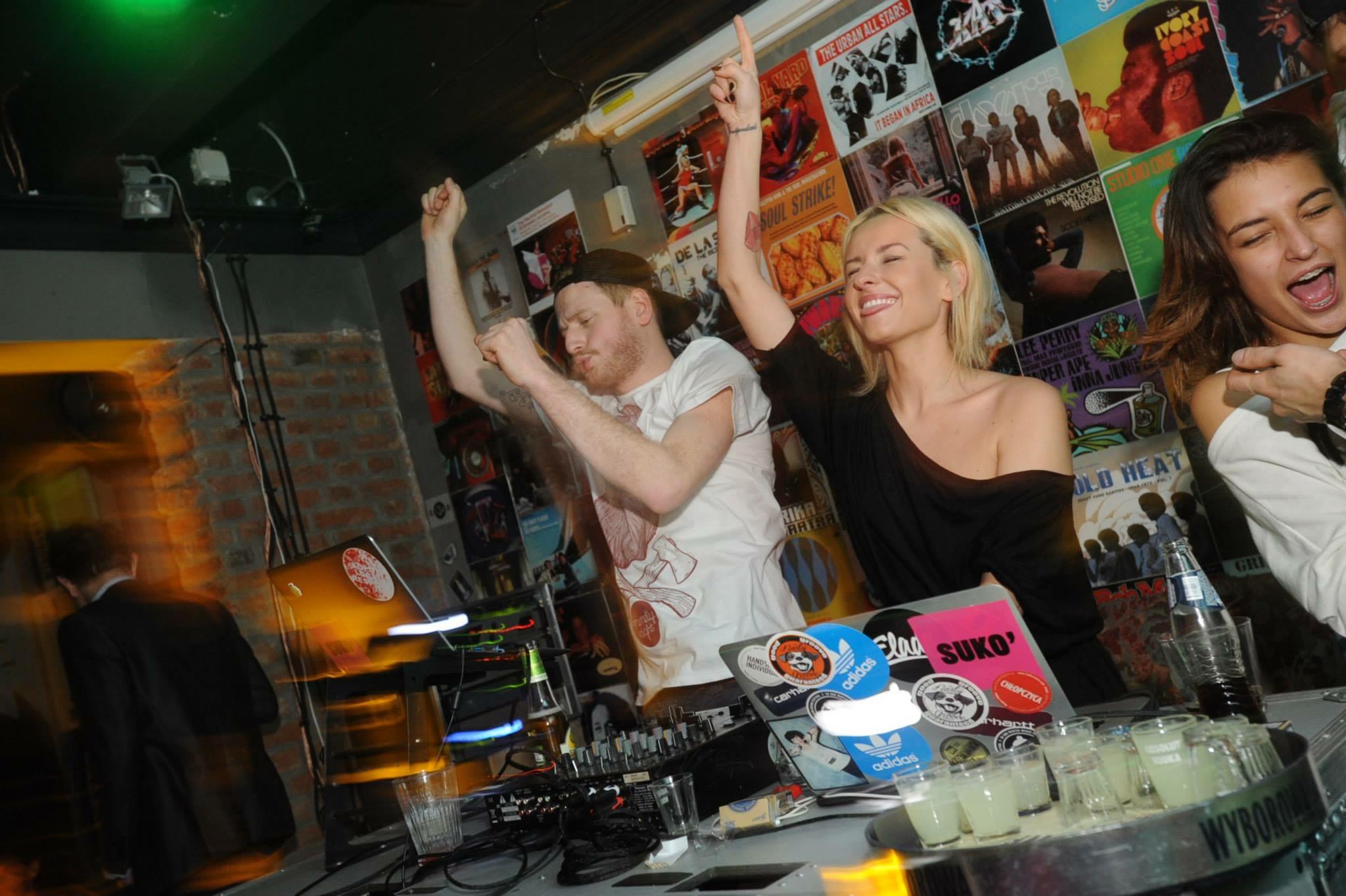 Na zdjęciu widzimy dwóch didżejów - dziewczynę i chłopaka. Mają ręce w górze i tańczą.