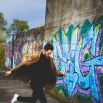 Mężczyzna z ciemnymi włosami i zarostem, ubrany w czarny golf i brązowy płaszcz i białe buty biegnie wzdłuż ściany z graffiti