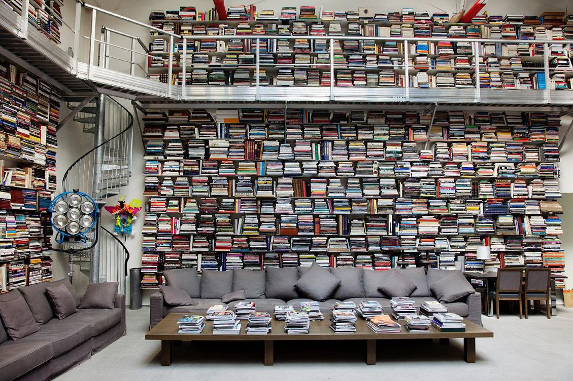 Fotografia kolorowa ukazująca imponującą domową bibliotekę. Na pierwszym planie widać stół, na którym znajduje się wiele książek i magazynów, za stołem jest ogromna szara sofa z licznymi poduszkami. Za sofą na całej ścianie, aż po sufit ułożone są książki i magazyny.