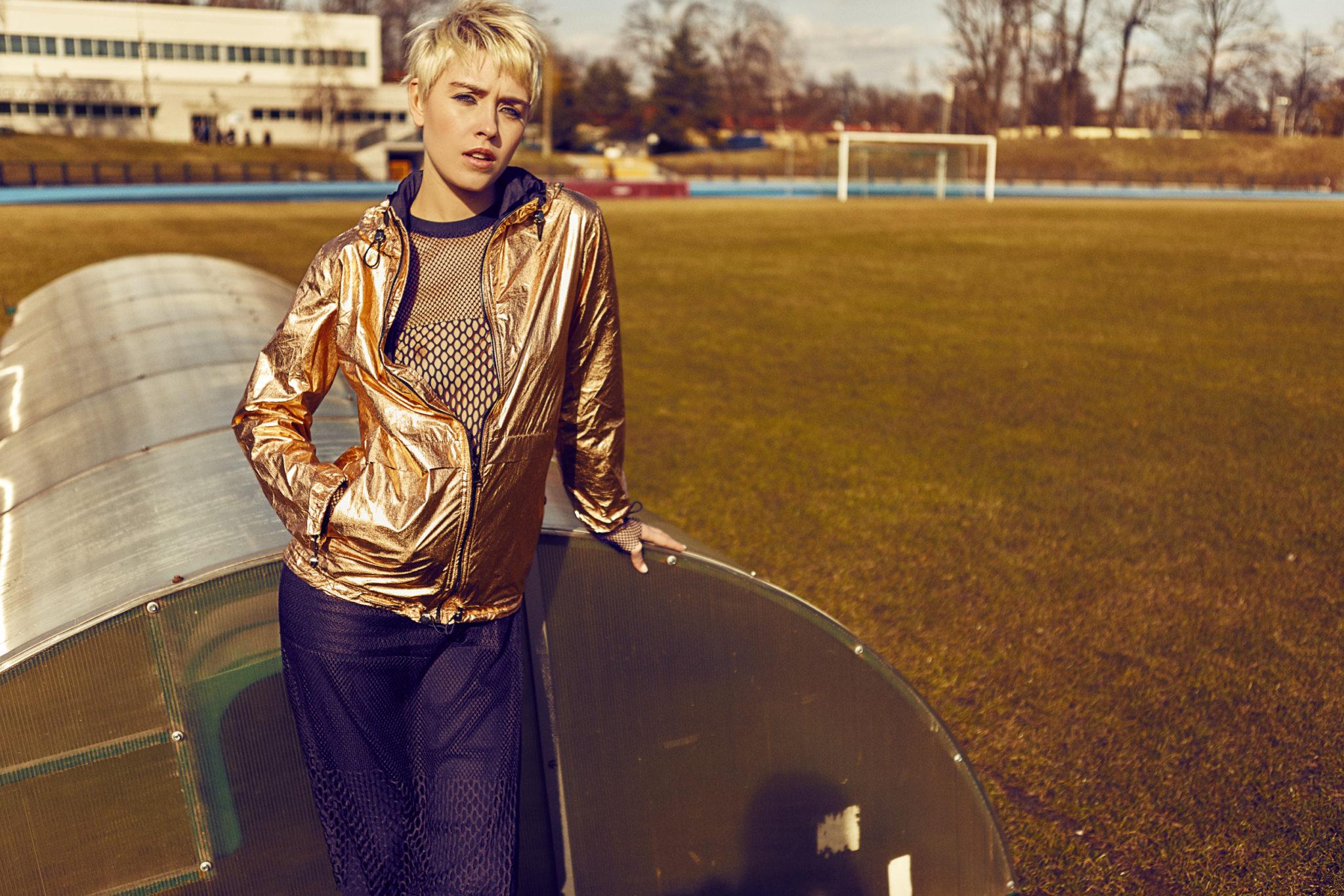 Dziewczyna stojąca na boisku w granatowych spodniach i złotej kurtce