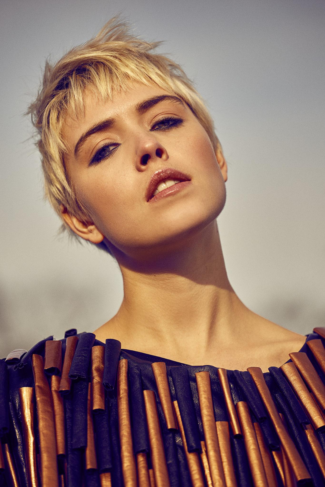 Portret dziewczyny w krótkich blondwłosach i bluzce z miedzianymi elemetami