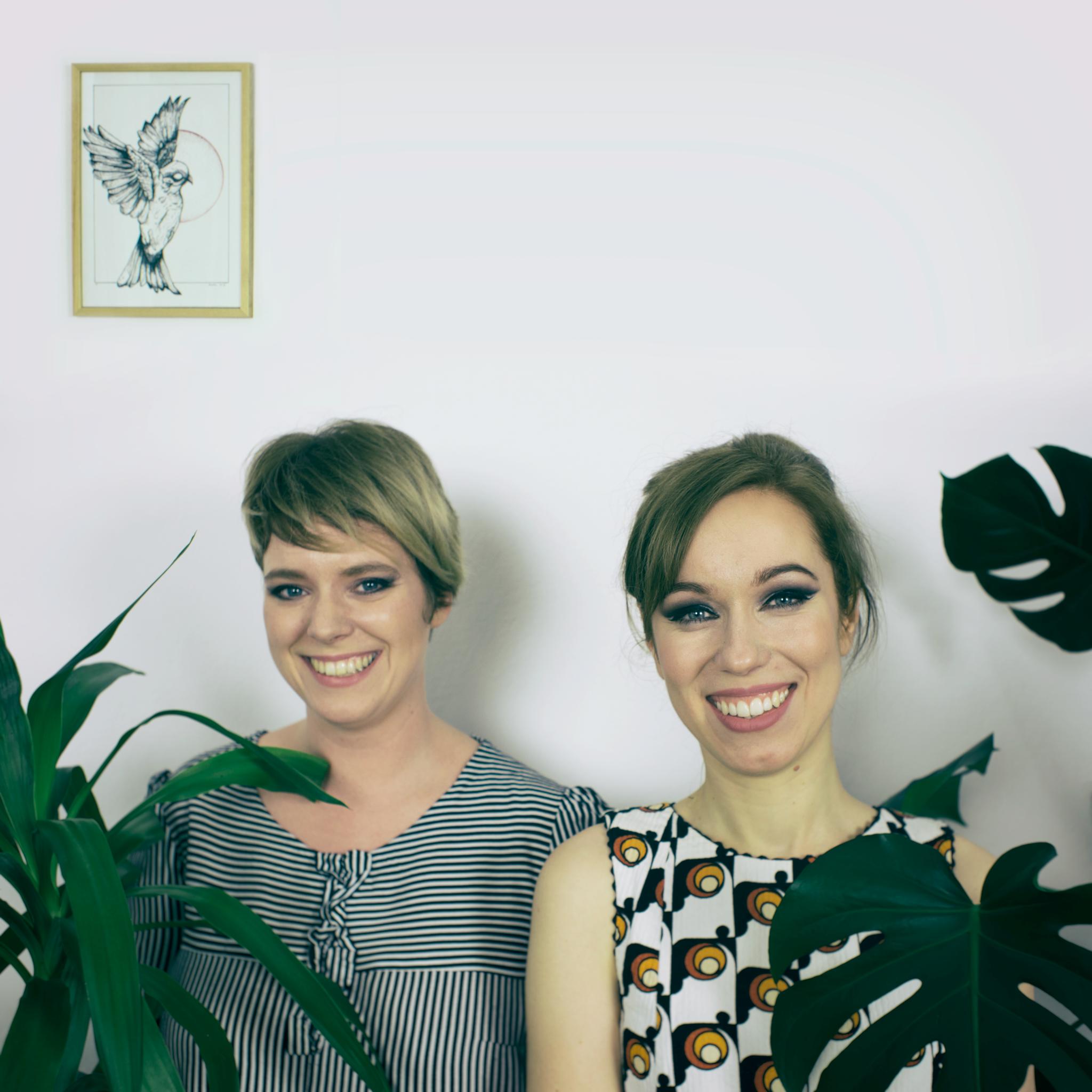 Dwie uśmiechnięte dziewczyny pomiędzy zielonymi roślinami