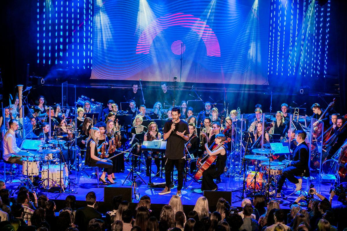 Mężczyzna stojący na scenie, trzyma mikrofon w ręku, z tyłu orkiestra