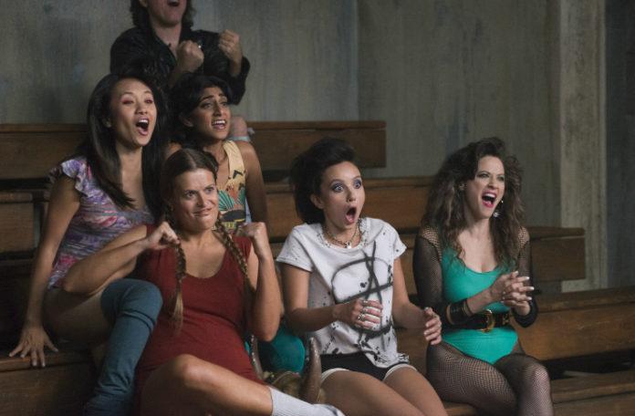 Grupa dziewczyn ubrana w ubrania z lat 80. siedzi na trybunach