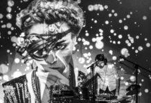 Mężczyzna stojący przy konsolecie, w tle wizualizacja z twarzą kobiety, zdjęcie czarno-białe