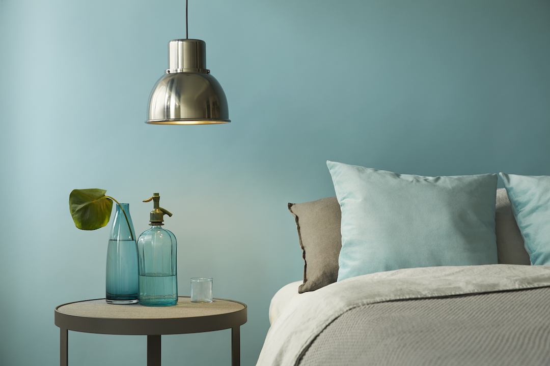 Sypialnia z łóżkiem i stolikiem utrzymana w niebiesko-szarej tonacji