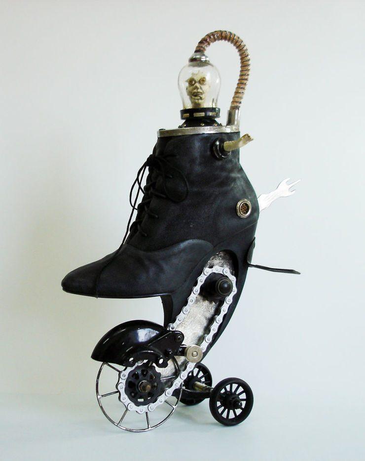 Rzeźba przypominająca but, który zamiast podeszwy ma surrealistyczne koła
