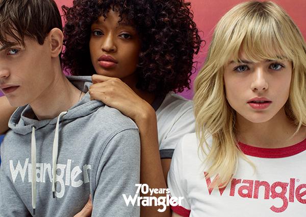 Chłopak w szarej bluzie, dziewczyna w kręconych włosach i dziewczyna w blond włosach z biało-czerwoną koszulką z napisem Wrangler
