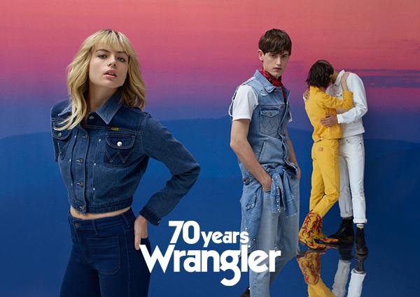 Dziewczyna w dopasowej kurtce jeansowej i jeansach z wyoskim stanem, obok chłopak w jasnych jeansach i kamizelce, dalej całująca się para: ona ubrana w żółty komplet, on na biało