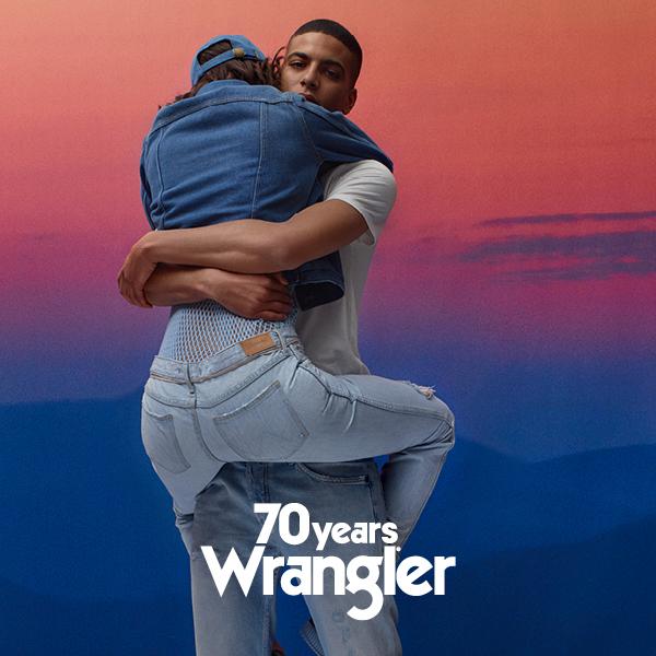 Czarnoskóry chłopak trzymający dziewczynę obejmującą go nogami, ubraną w jeansy