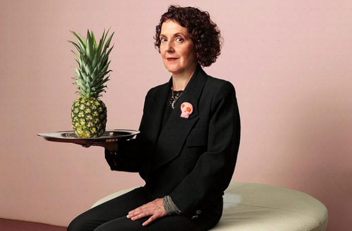 Fotografia kolorowa. Na zdjęciu na różowym tle widać siedzącą kobietę. Kobieta ma czarne włosy do brody, lekko kręcone. Ubrana jest w czarny garnitur, do klapy marynarki przypięta ma broszkę - różową czaszkę. W prawej ręce na tacy trzyma ananasa.
