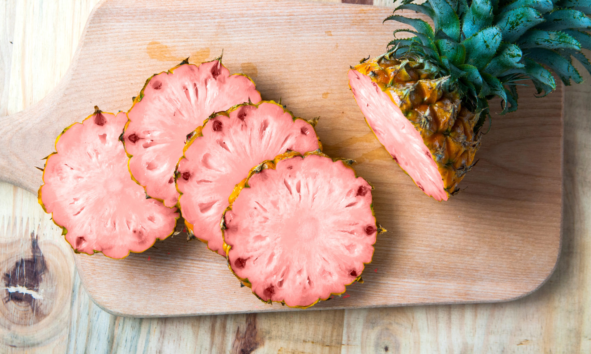 Zdjęcie ananasa pokrojonego na cztery kawałki. Owoc leży na desce do krojenia. Widać różowy, genetycznie zmodyfikowany owoc.