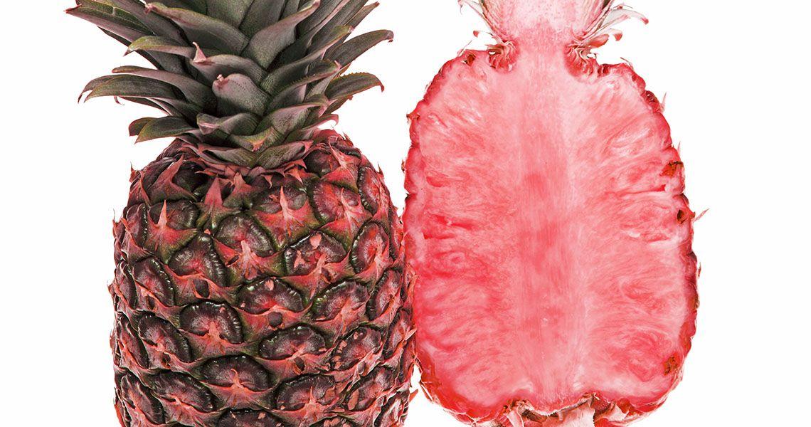 Na zdjęciu widoczny jest przepołowiony anansa, którgo owoc jest różowy.