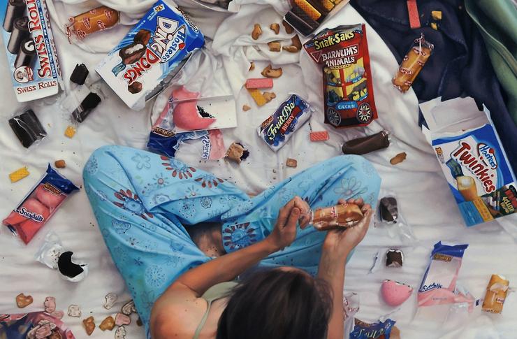 Dziewczyna siedząca na łóżku w otoczeniu róznego rodzaju przekąsek