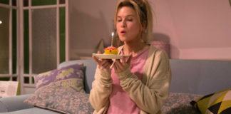 Kobieta siedząca na kanapie w piżamie, trzymająca w ręku babeczkę z wbitą świeczką