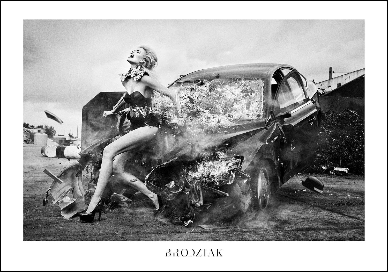 Czarno-białe zdjęcie kobeity siedzącej na zniszczonym samochodzie