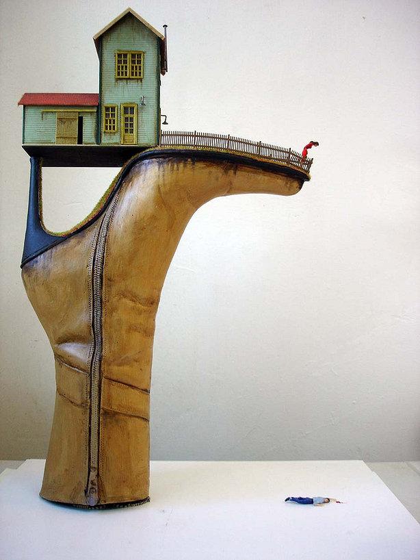Rzeźba przypominająca odwrócony but z domem leżącym pomiędzy obcasem a cholewką