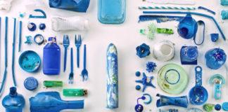 Fotografia reklamowa. Na białym tle poukładane są równo, niebieskie śmieci, takie jak plastikowe widelce, słomki, butelki itp. Na środku widać biało niebieskie dildo.