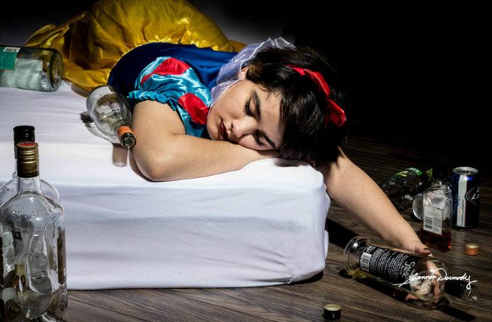 Księżniczka śpiąca na łóżku w otoczeniu pustych butelek