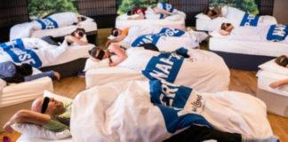 grupa ludzi w opaskach na oczach spiacych w lozkach w bialej poscieli