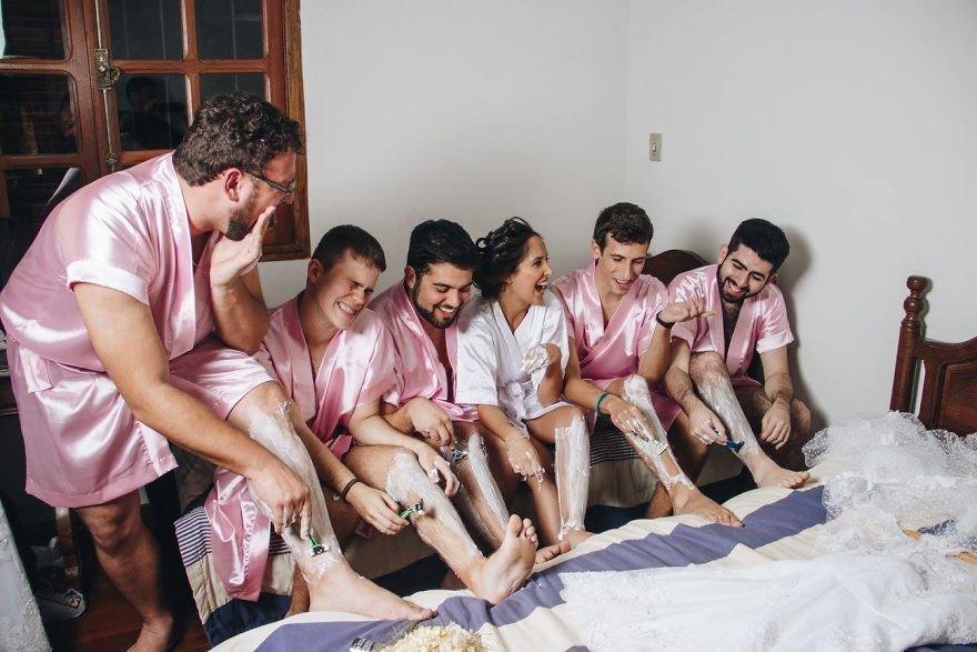 Kobieta w białym szlafroku i pięciu mężczyzn w różowych szlafrokach golą sobie nogi