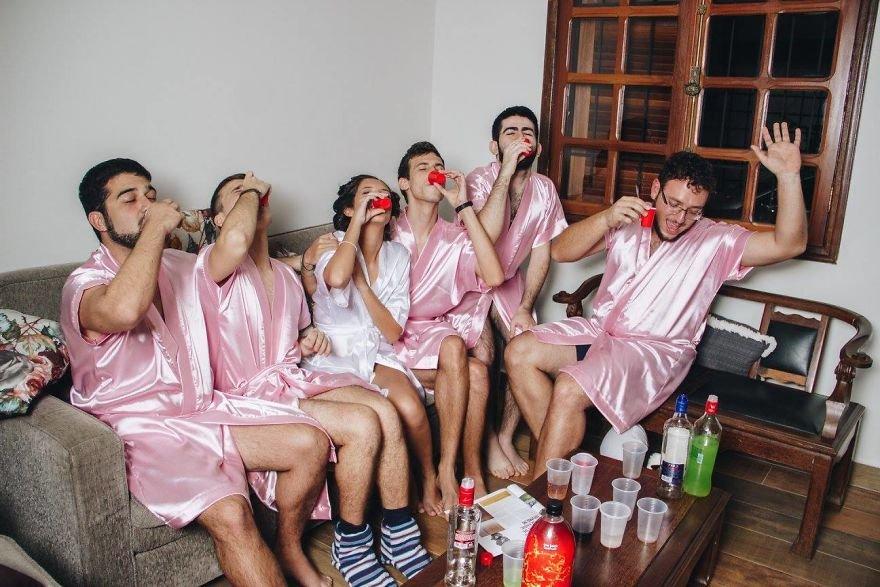 pieciu mezczyzn w rozowych szlafrokach i kobieta w bialym szlafroku pija alkohol z czerwonych kubeczkow