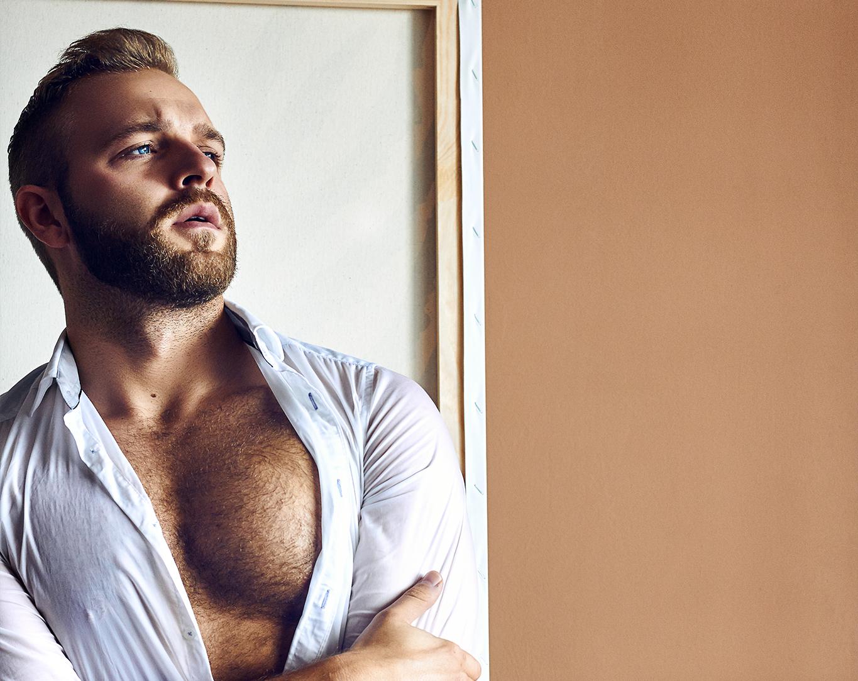 Mezczyzna w rozpietej bialek koszuli ukazujacy umiesniona piers, ma brode i was, zamyslony patrzy w prawa strone