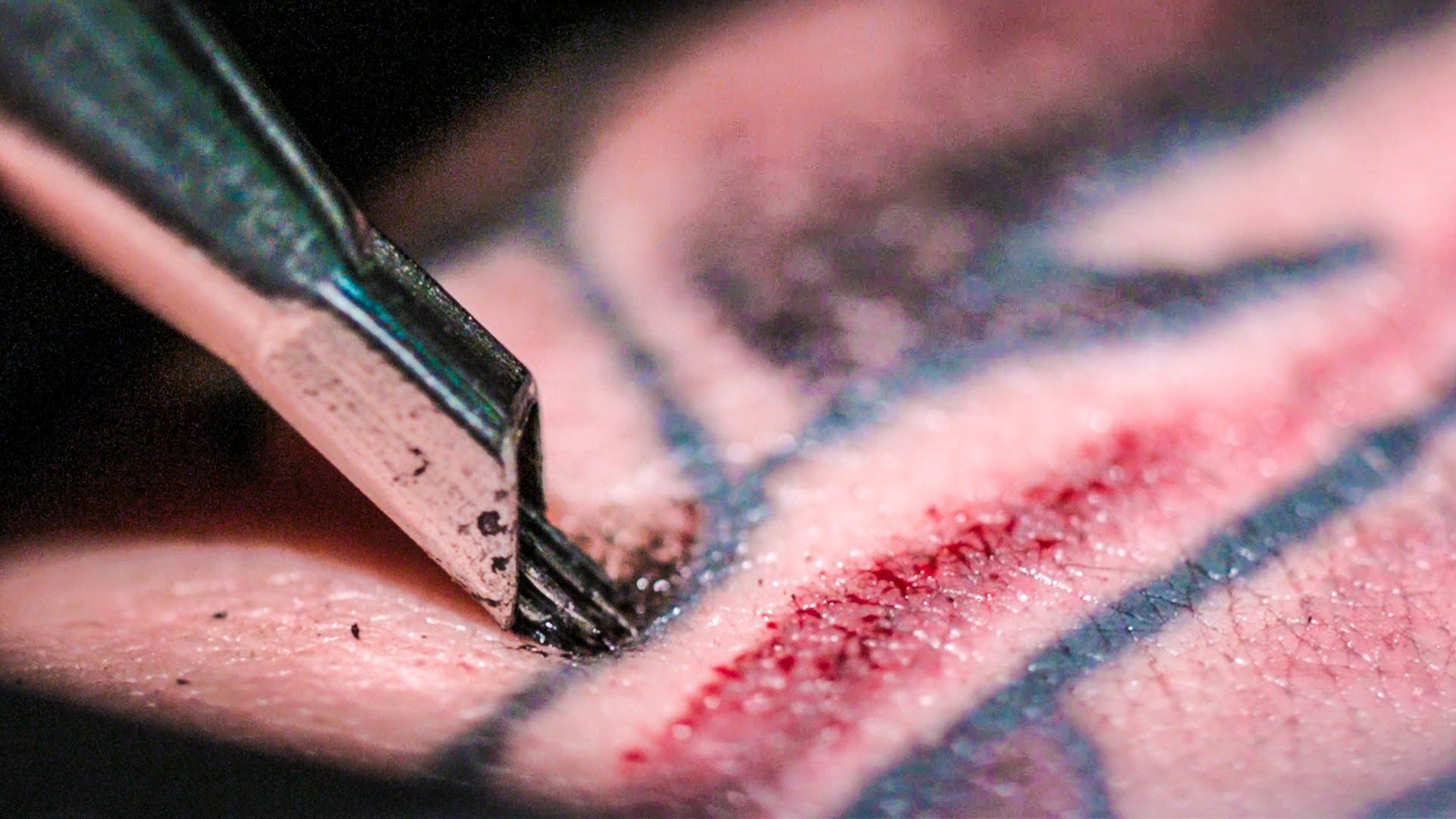 Zdjęcie przedstawia prces tatuowania z bliska