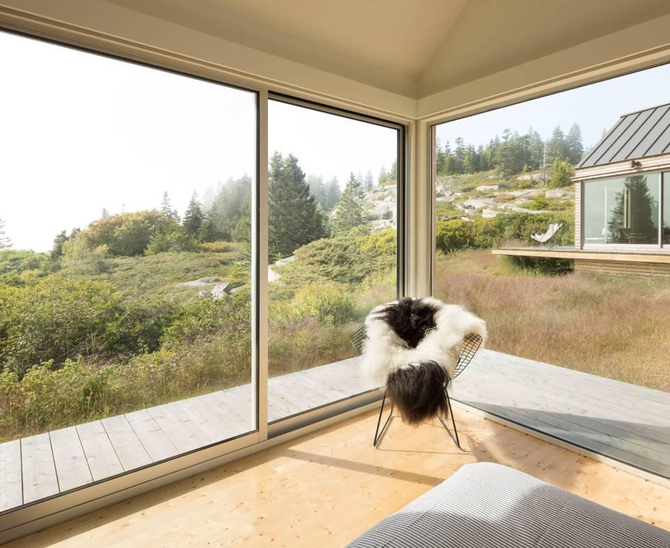 Fotografia kolorowa. Zdjęcie pokazuje dwa duże okna, kadr z wnętrza pokoju pokazuje widok, na zbocze wzniesienia, zielną trawę kilka szarych kamieni, zielone drzewa iglaste.Po prawej stronie widać fragment jasnego, drewnianego domku. Okna usytuwane sa na rogu dwóch ścian, w tym roku stoi krzesło, na którym ułożono futrzaną skórę w czarno-białe łaty.