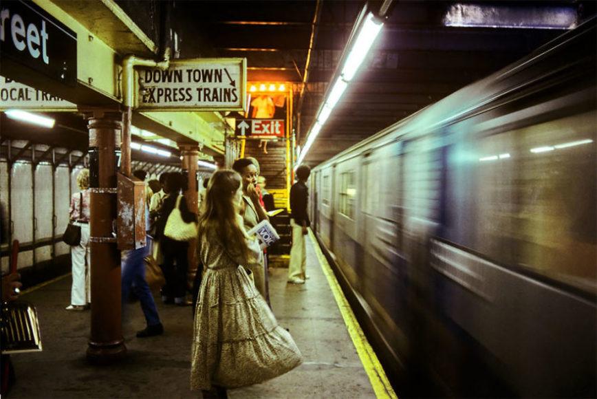 zdjęcie przedstawia pociąg wjeżdżający na stację i ludzi stojących przy krawędzi peronu