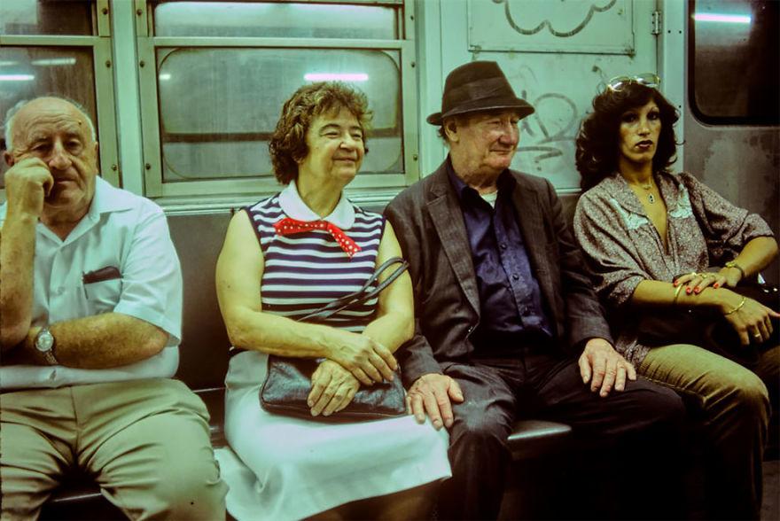 zdjęcie przedstawia dwie kobiety i dwóch mężczyzn siedzących wewnątrz wagonu pociągu