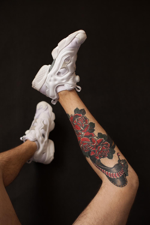 męskie nogi z tauażem na łydce i białymi butami