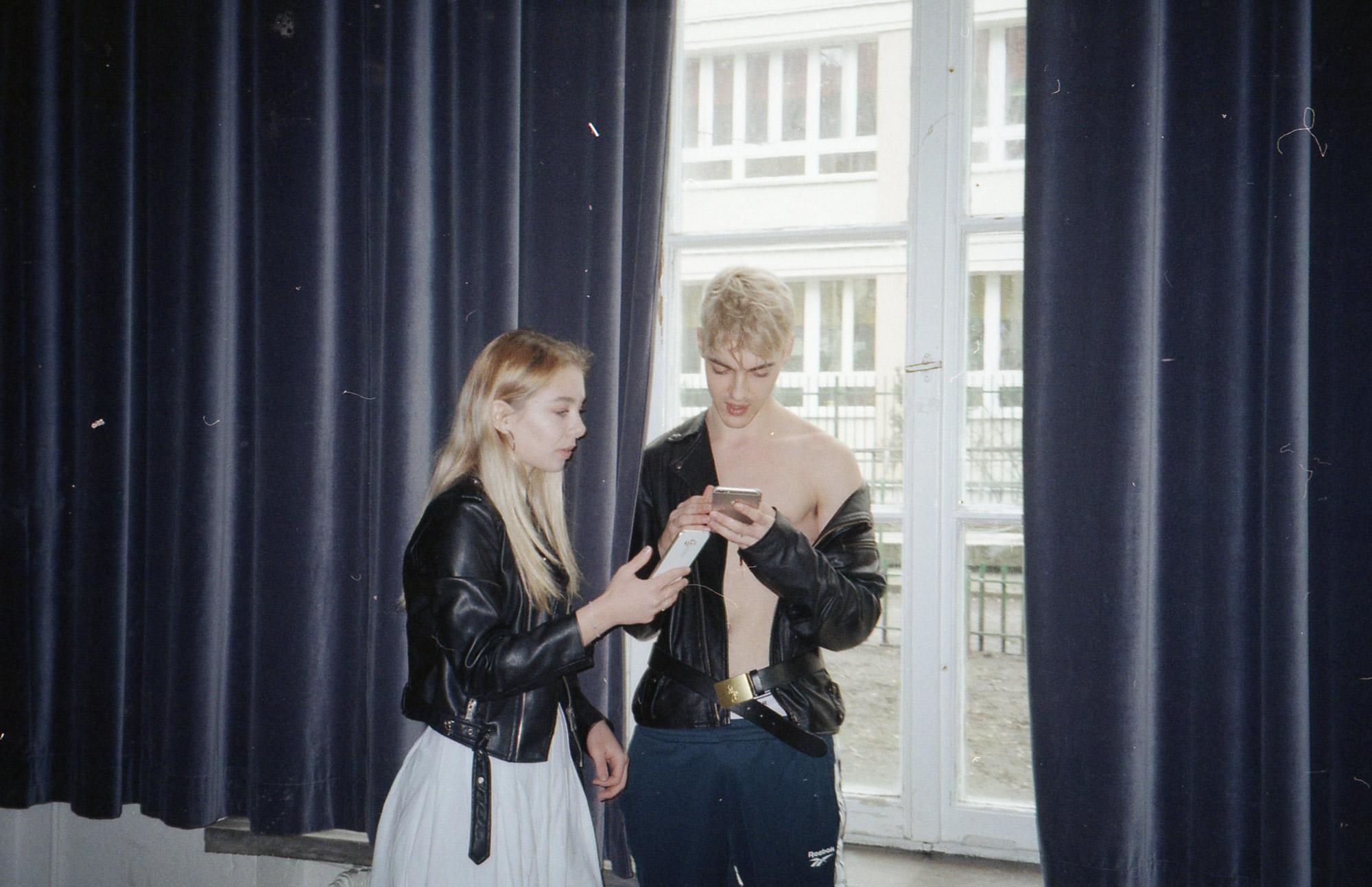 Dziewczyna w białej spódnicy i skórzanej kurtce i chłopak w skórzanej kurtce bez koszulki