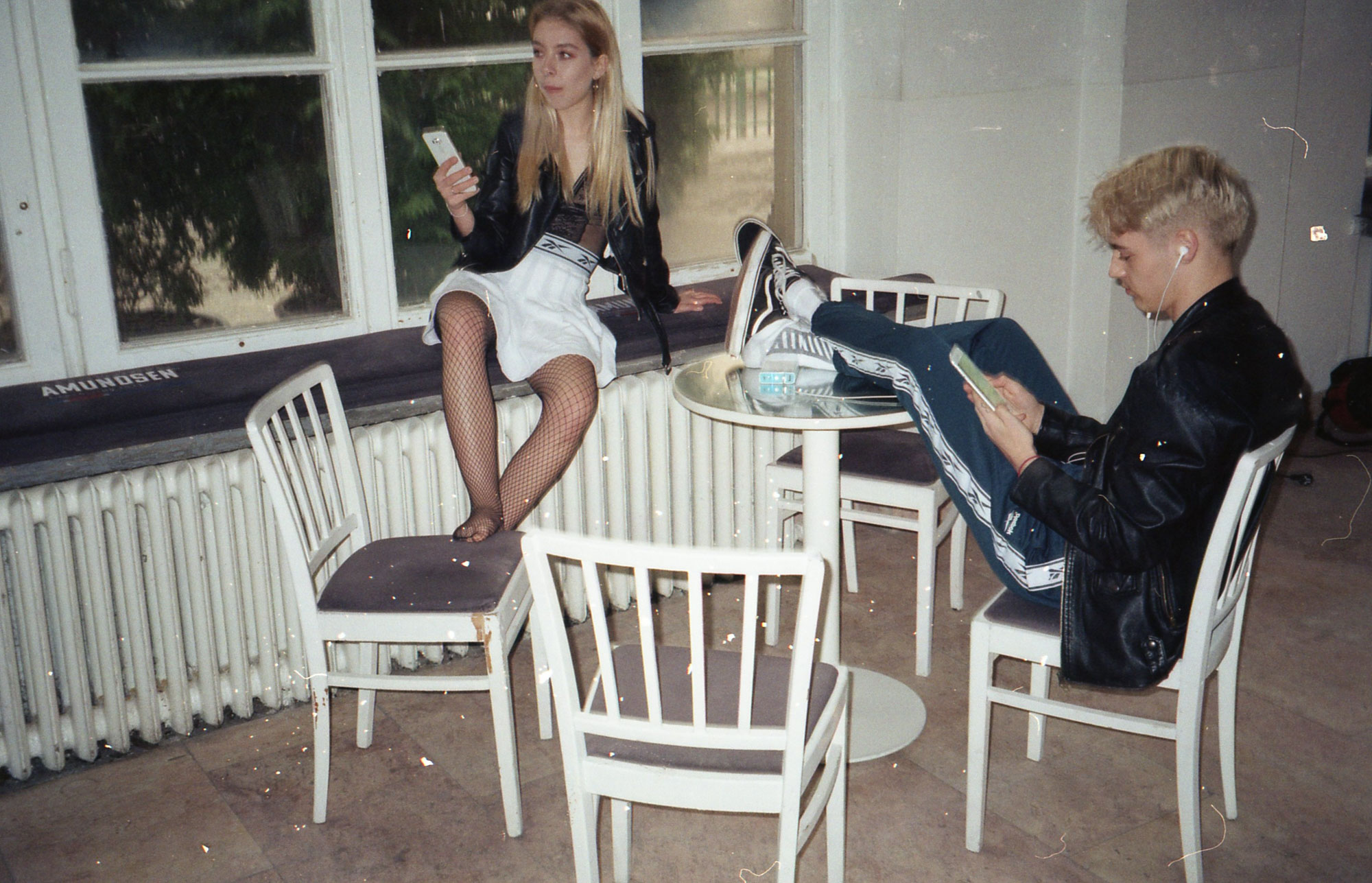 Chłopak siedzący na krześle z nogami na stole i dziewczyna siedząca na parapecie z telefonem w ręku