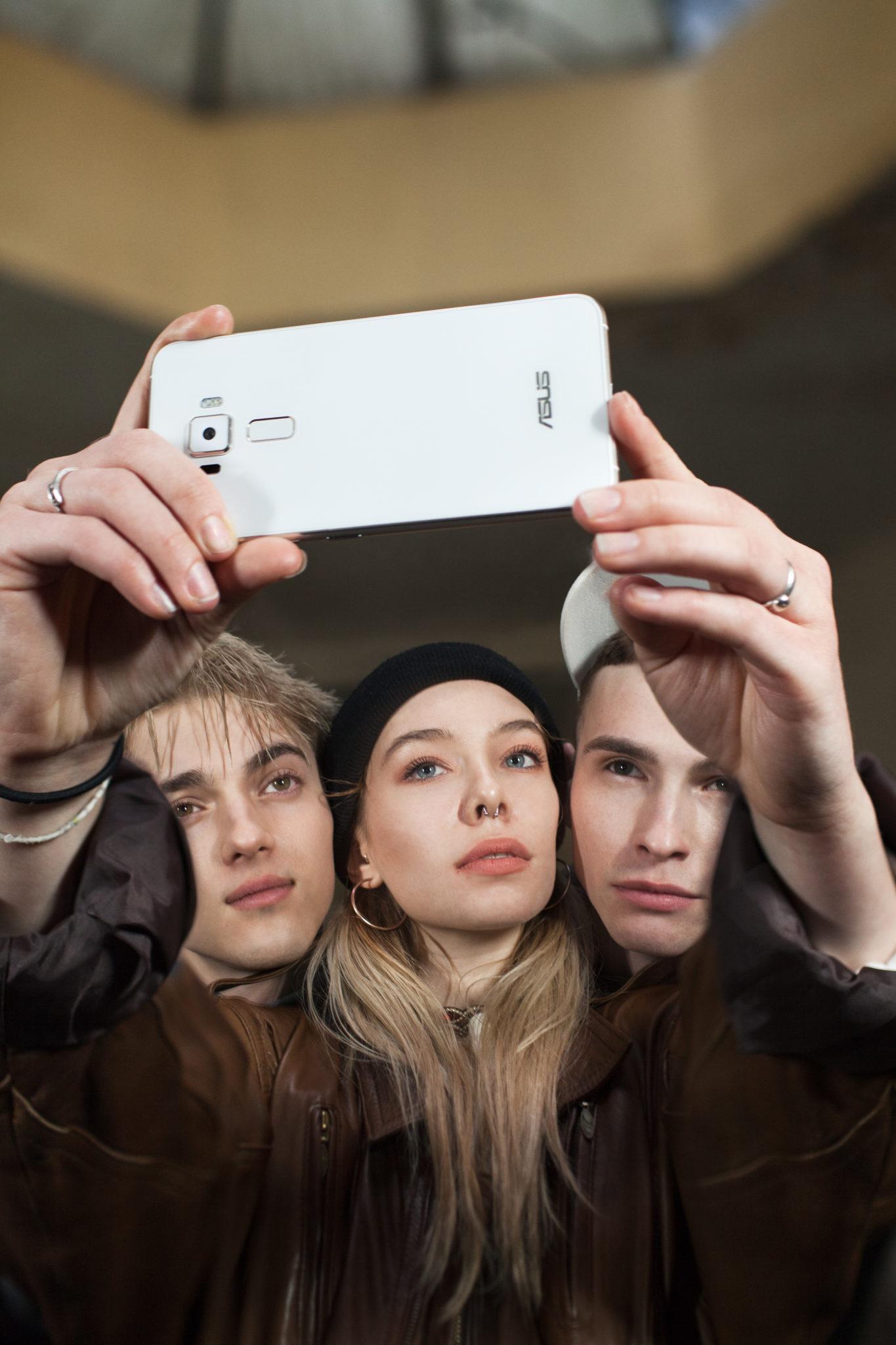 Dwoch chłopaków i dziewczyna robią sobie selfie białym smartfonem
