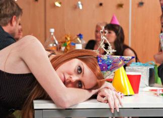 na zdjęciu znajdują się cztery osoby. kobieta na pierwszym planie leży na blacie stołu. jest ubrana w czapkę typu stożek