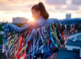 Dziewczyna stojąca tyłem w kurtce z doczepionymi frędzlami