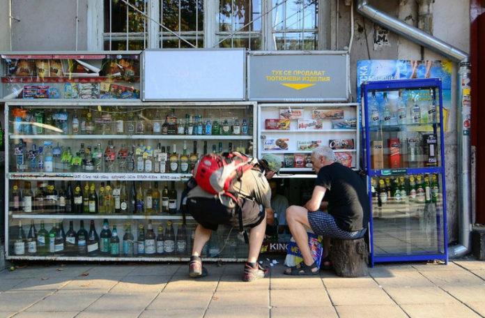 Zdjęcie dwóch panów, z których jeden siedzi na pieńku a drugi kuca w celu zrobienia zakupów w kiosku, który znajduję się w piwnicy budynku, a jego kasa wychodzi na chodnik i znajduję się na wysokości kolan. Wśród bogatej oferty produktów niepodzielnie króluje alkohol.