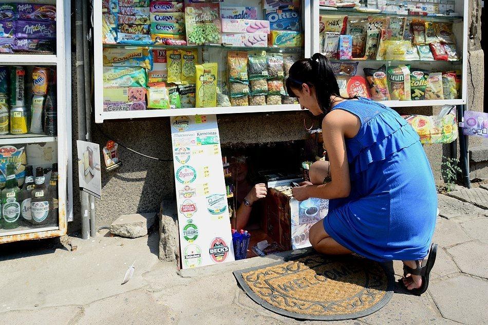 Kobieta klęcząca przy nisko osadzonym kiosku w ścianie budynku