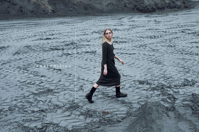 Fotografia kolorowa utrzymana w kolorystyce szaro-niebieskiej. Na środku widać idącą kobietę, blondynka, w czarnej obszernej sukience sięgającęj połowę łydki, do tego czarne buty z wysoką cholewką. Kobieta odwraca głowę i patrzy za siebie.