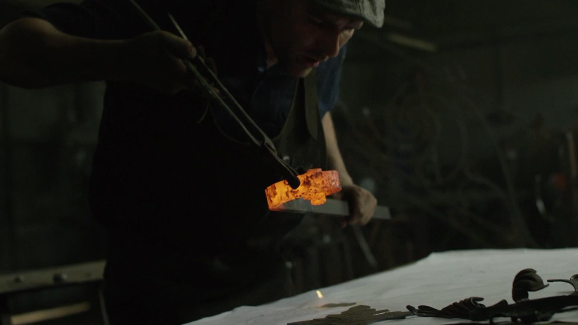 Mężczyzna chuchający na rozgrzane żelazo