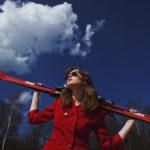 Dziewczyna ubrana w czerwone spodnie i czerwoną marynarkę trzyma za plecami, na karku czerwone narty